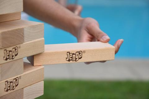 someone pulling out a giant jenga block - Bachelorette Party Activities for the Casual Bride
