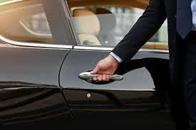 Chauffeurs hand opening black car door - Bachelorette Party Activities for the Break the Bank Bride