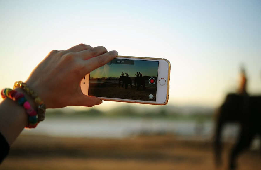 Hand holding a phone screen recording a video - Bachelorette Party Activities for the Budget Bride
