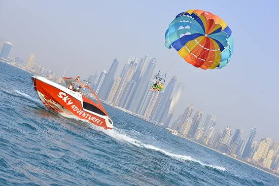 Speedboat pulling windsurfers in front of the Dubai Skyline - Bachelorette Party Activities for the Active Bride