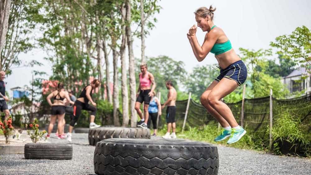 Women jumping in and out of tyres in sportswear Bachelorette Party Activities for the Active Bride