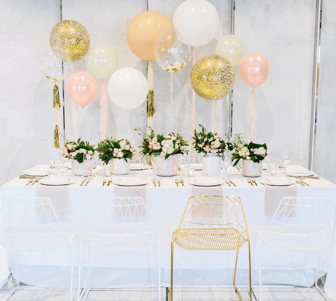 White table set up with peach, pink and gold balloons - Bachelorette Party Activities for the Break the Bank Bride