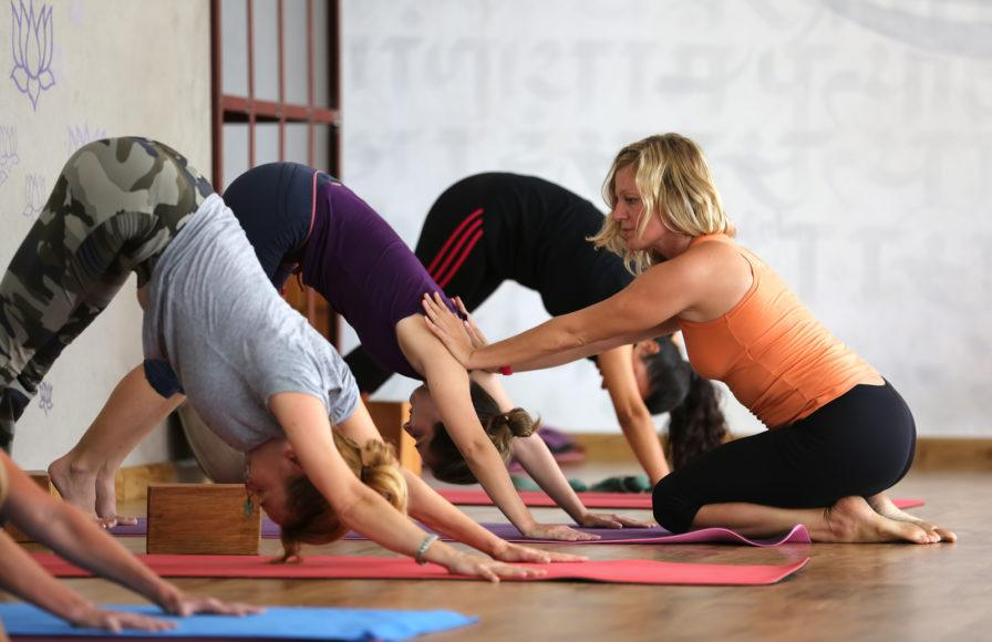 Yoga instructor helps a class  - Bachelorette Party Activities for the Active Bride