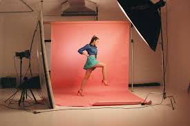 Woman striking a dynamic pose in front of red backdrop in a studio - Bachelorette Party Activities for the Break the Bank Bride