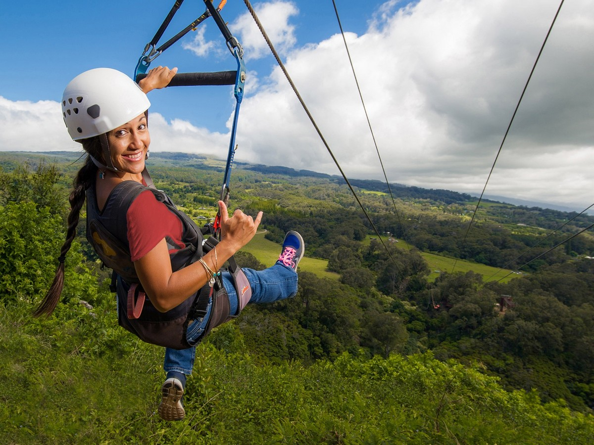 Woman smiling from zipline over treetop canopy - Bachelorette Party Activities for the Active Bride