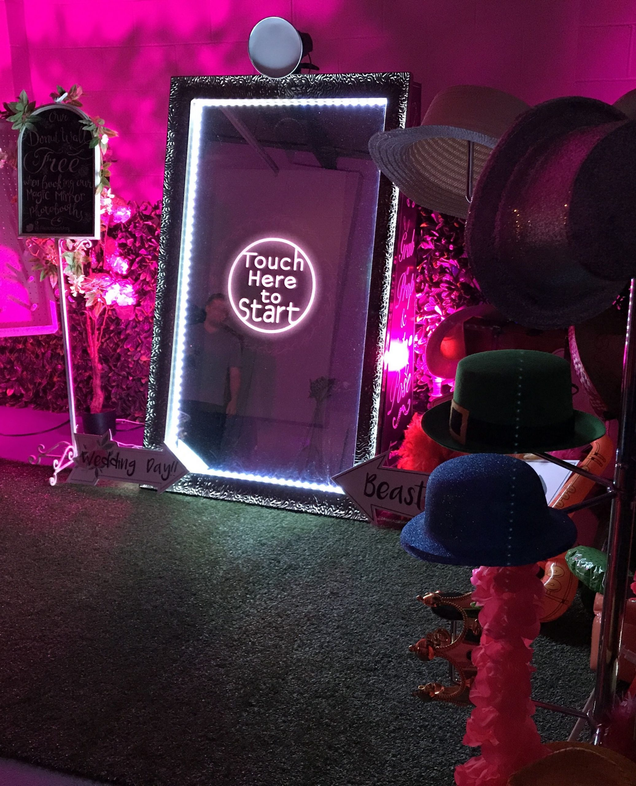 """A large digital mirror saying """"Touch here to start"""" set up against pink lights Bachelorette Party Ideas for the Break the Bank Bride"""