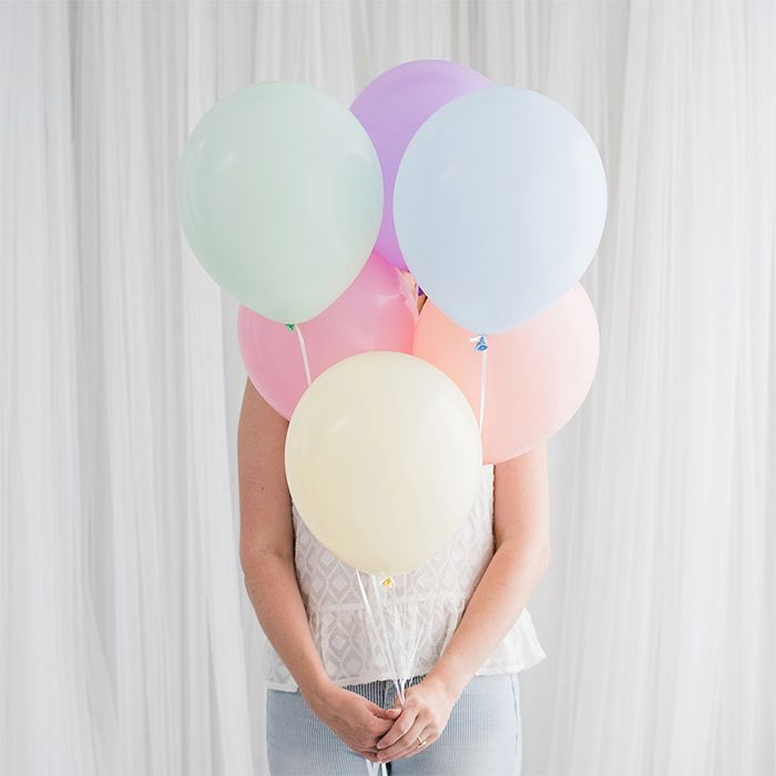 A woman holding a bunch of pastel balloons - Bachelorette Party Decor for the Budget Bride