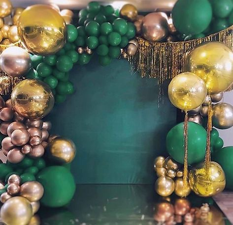A green wall with gold and green balloon arch - Ideas for a Loki Themed Hen weekend Decor